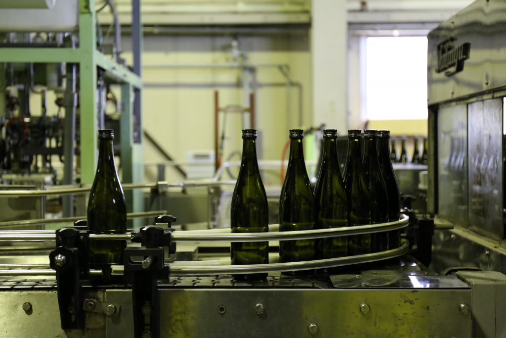sake bottles lined up for filling in a brewery