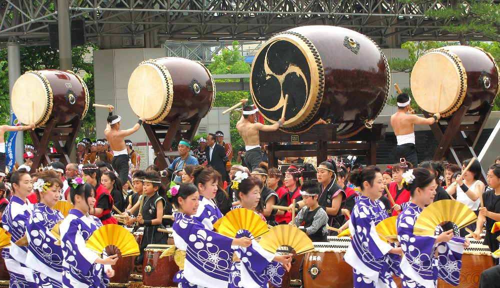 a hundred taiko drums in front of Kanazawa Station's drum gate at the Hyakumangoku Festival Parade