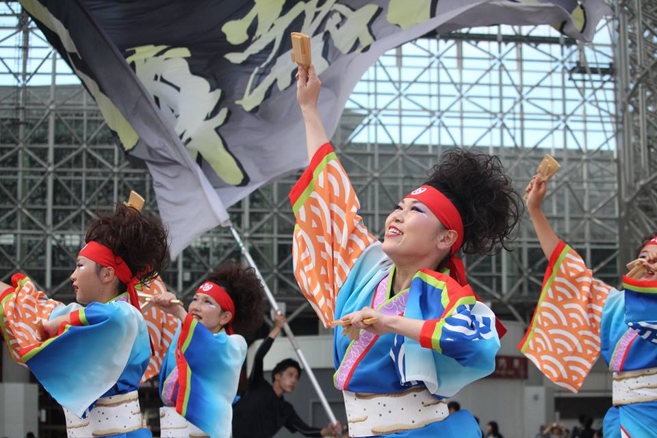 Yosakoi team with flags and clappers under Kanazawa Stations Motenashi Dome, by Tamaya Greenlee