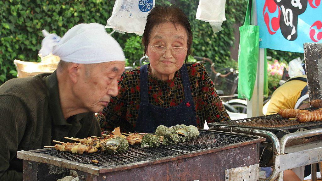 An older couple check their barbecue progress at a food fair in Kanazawa, Japan