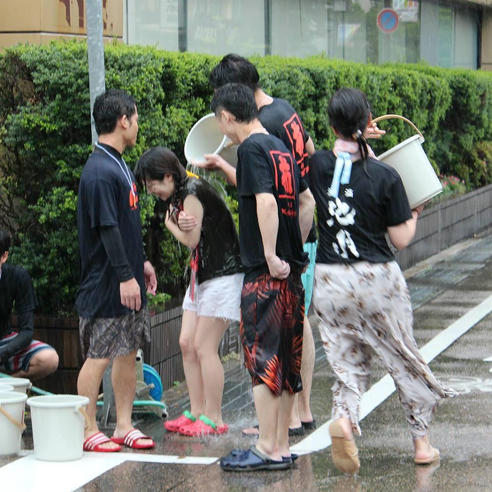 Pouring water at Kakinokibatake's Mizukake Festival in Kanazawa, Japan