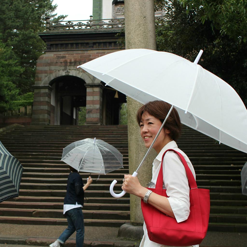 Fumie, Morning Tour Director at Kaname Inn, in front of Oyama Shrine in Kanazawa, Japan