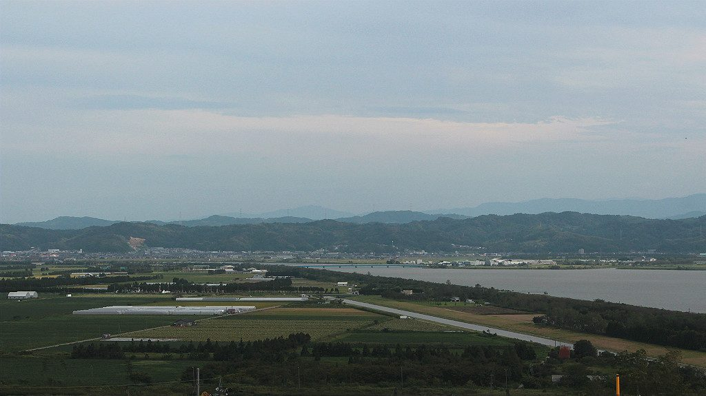 View of the Japanese Alps and the Kahoku Lagoon near farmland, in Uchinada, Japan
