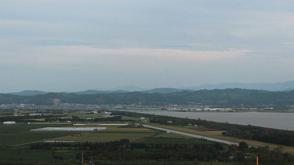 View of the Japanese Alps and the Kahoku Lagoon near farmland, in Uchinada, Japan