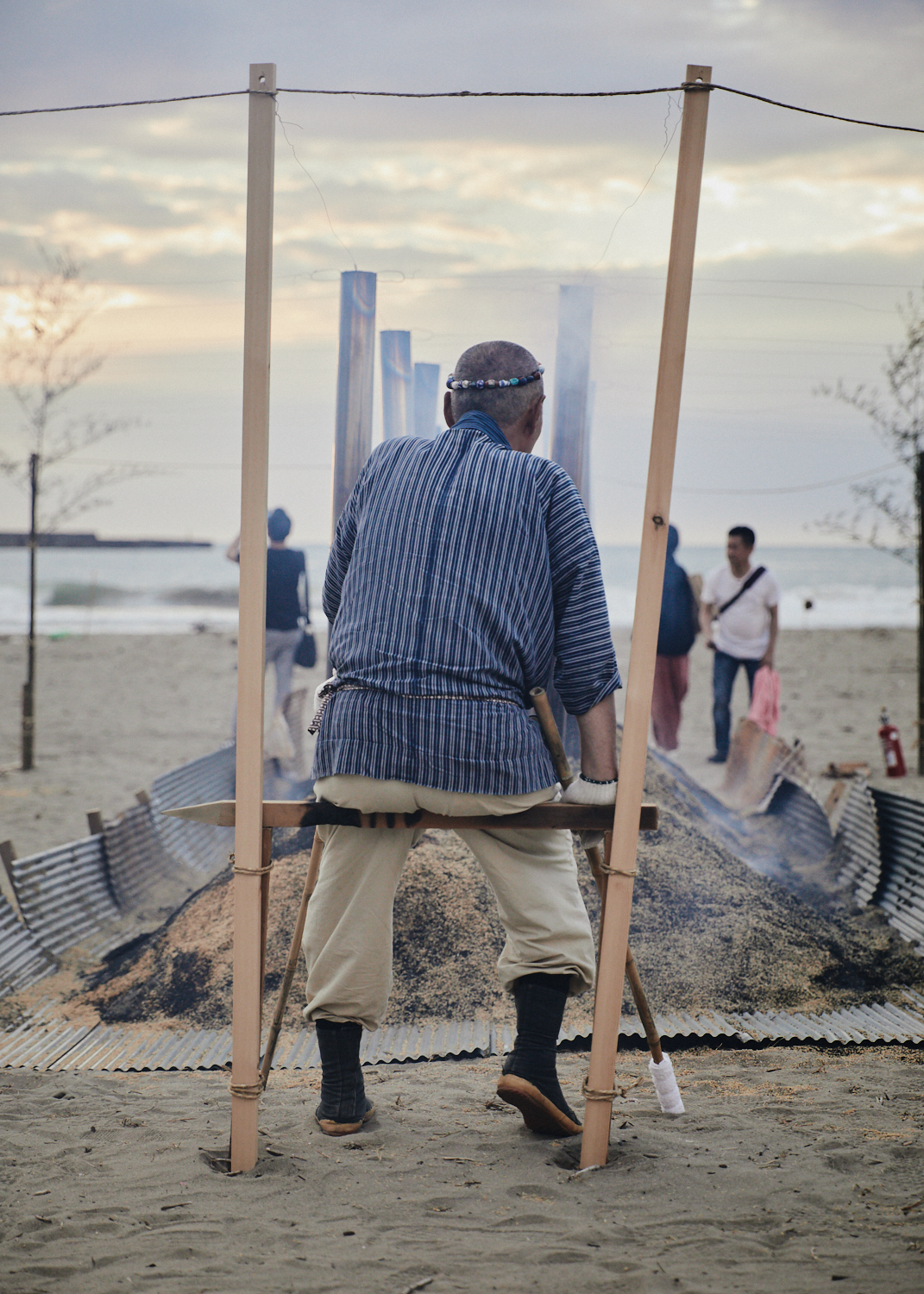 Master Iida overseas the slow burn of the wild kiln of noyaki, earthenware baking on Kanaiwa Beach in Kanazawa, Japan.