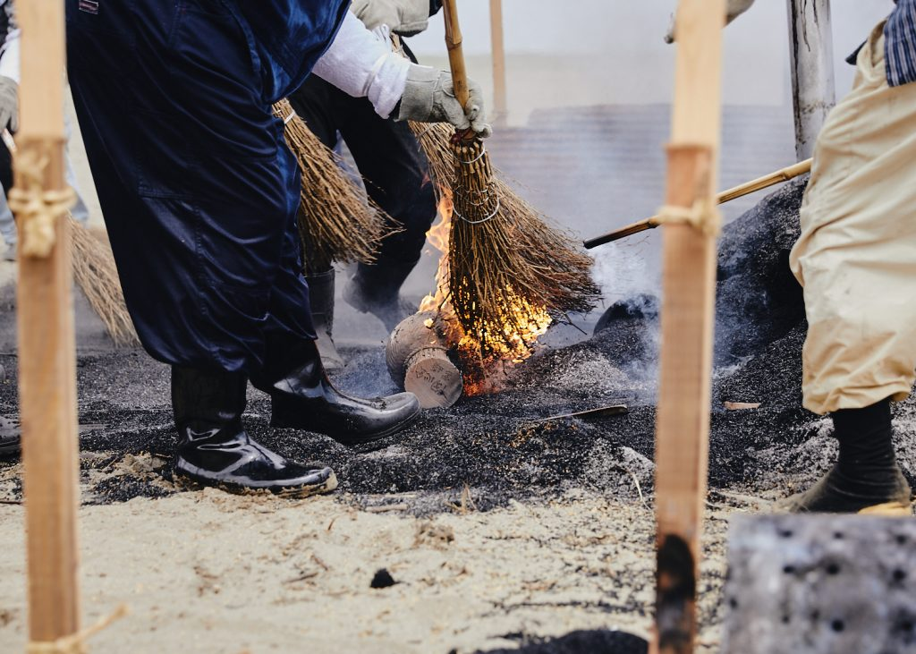 The brooms that brush the burning rice hulls catch fire as they reveal the completed earthenware pottery pieces.