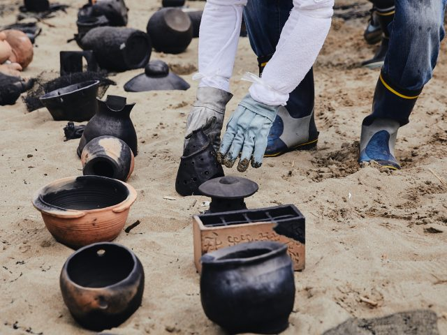 Baked earthenware from the Noyaki wildfire kiln takes on variegated colors of adobe, black, and silver.