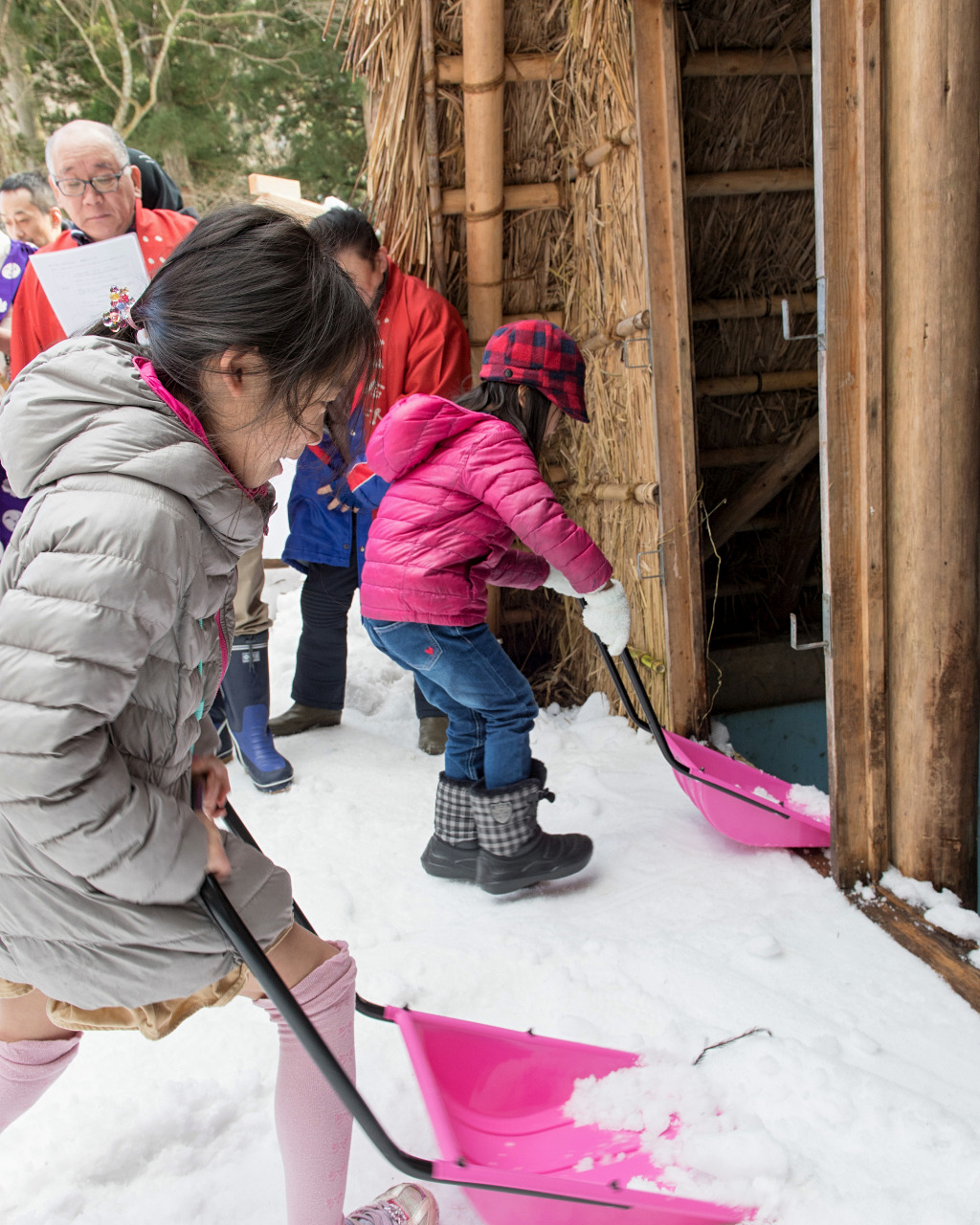 Children shoveling snow into the Himuro Koya in Yuwaku