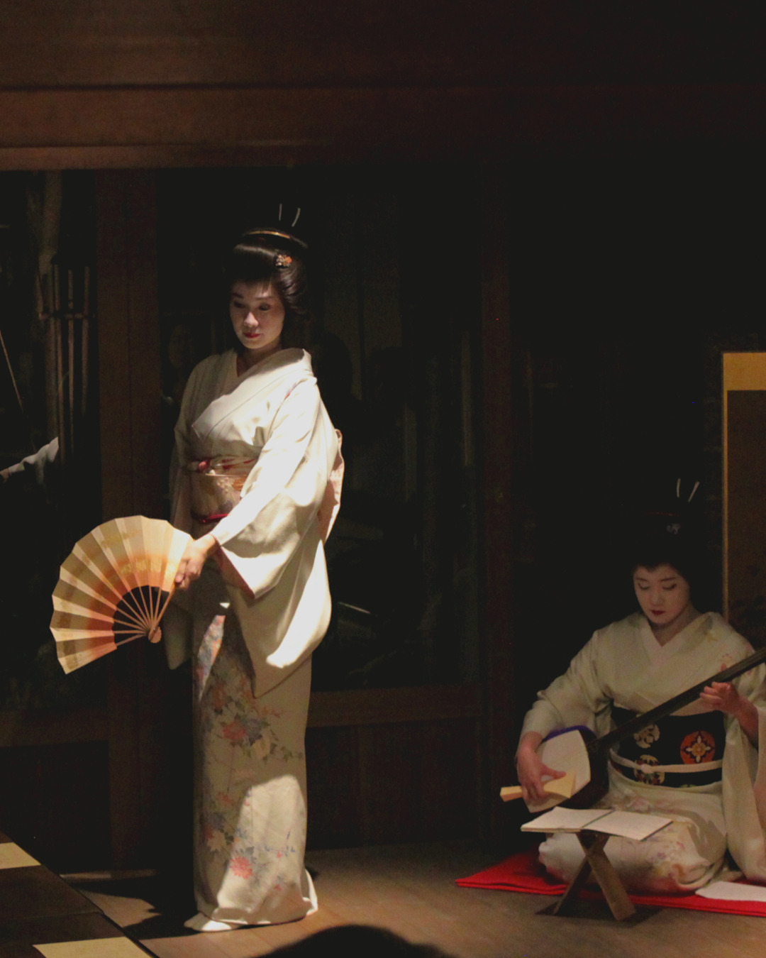 Geisha performing under a spotlight, at the In Kanazawa House performance event