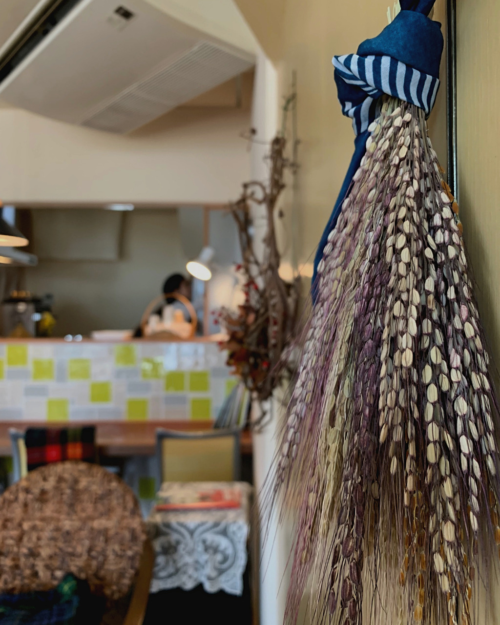 Dried buff and dark purple grains hang from the wall at Ihanoha Vegan Cafe in Kanazawa, Japan