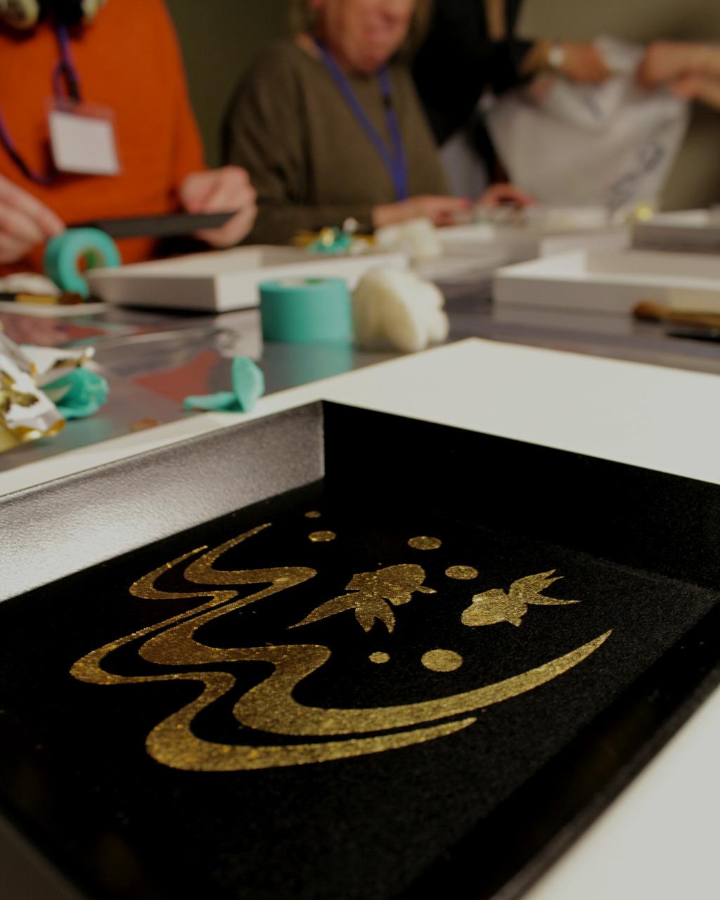 Stenciled gold leaf plate at gold leaf workshop in Kanazawa