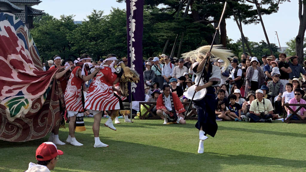 Lion dancers, using the uniquely local style of lion head, dance for the crowds at Kanazawa Castle during the Hyakumangoku Festival