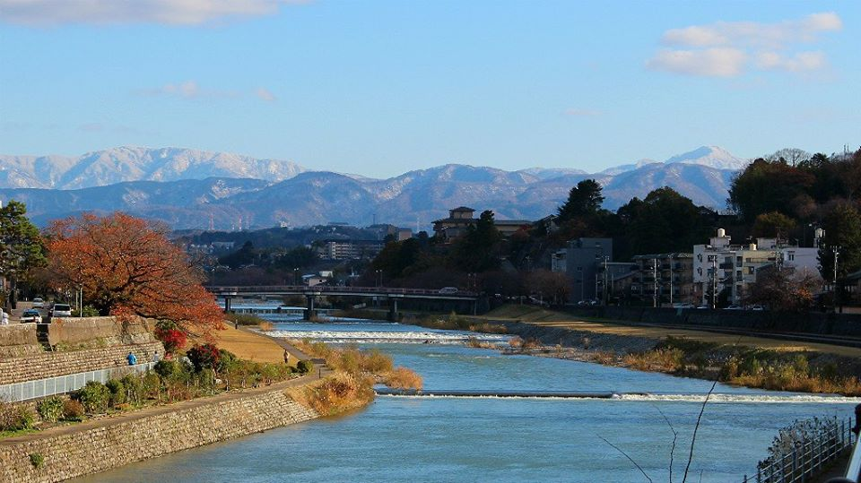 The Saigawa River in Kanazawa in autumn, with mountain view.