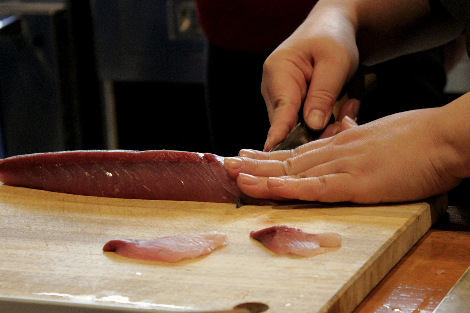 Naoko denonstrates the correct angle for cutting sashimi during her cooking class in Kanazawa, Japan