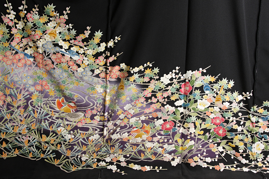 The bottom half of a fully open formal kimono, with a black background and kaga-yuzen imagery