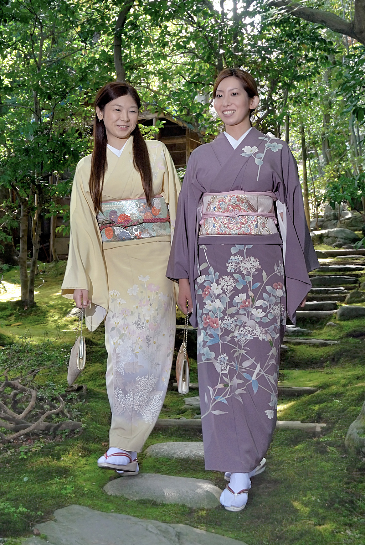 Two women wearing Kaga-yuzen silk kimono and walking through a garden