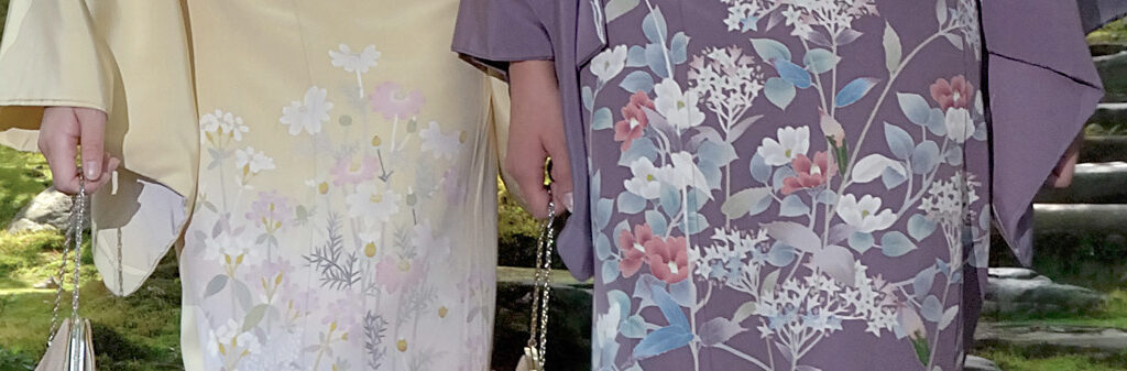 Close of up the skirt section of two Kaga-yuzen kimono, detailed with flowers, one purple and one yellow